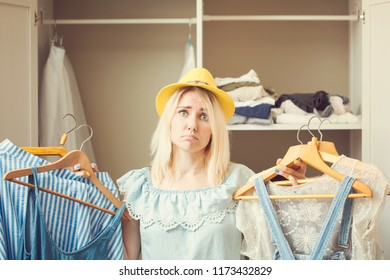 girl near a wardrobe with clothes can not choose what to wear. Heavy Choice Concept has nothing to wear