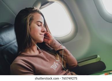Girl near the window in airrplane listening music in headphones