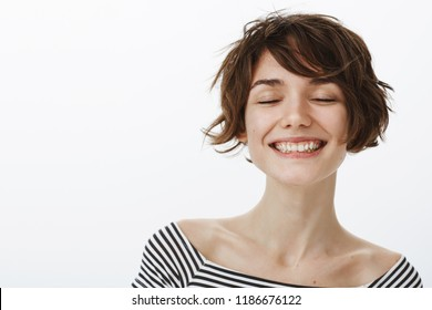 Girl never stops dreaming. Portrait of relaxed happy young female student in striped top, closing eyes and smiling joyfully, dreaming or being in great mood, standing relieved and calm over grey wall