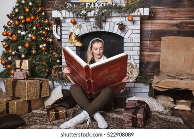 """The girl in the New Year's atmosphere. Around her there are a lot of gifts, a fireplace and a New Year tree. The girl reads the book """"New Year's Fairy Tales""""."""