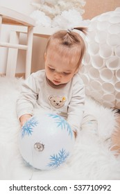 girl in a New Year's interior, playing with Christmas balls