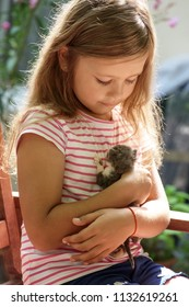girl with newborn kitten in her hands
