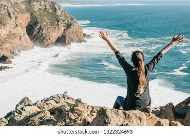 The girl next to the Atlantic Ocean in Portugal raises up her hands shows how pleased she is.