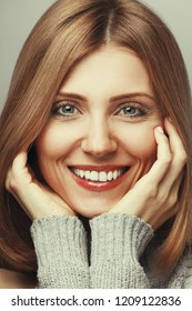 Girl Next Door, My fair lady, One Million Dollars Smile concept. Close up portrait of 30 years old young woman smiling wearing knitted sweater. Perfect shiny smile. Studio shot