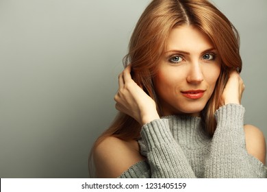 Girl Next Door, My fair lady concept. Close up portrait of 30 years old young woman smiling wearing knitted sweater over gray background. Copy-space. Studio shot