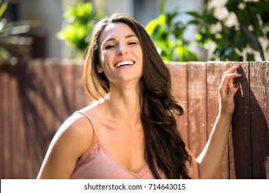 Girl next door type laughing with a fun playful energy outdoors on a sunny bright day