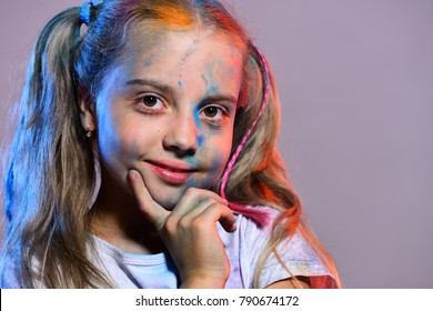 Girl with nice face isolated on purple background, copy space. Kid with ponytails touches cheeks. Schoolgirl has paint spots on face. Childhood and holiday concept.