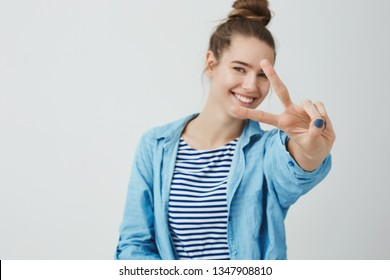 Girl not scared facing problems feeling lucky determined win smiling carefree having fun feeling joyful enjoying life leading healthy active lifestyle smiling broadly showing victory, peace gesture