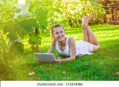 girl with notebook on green grass
