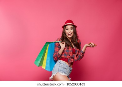 Girl with nude make up and curly hair posing at pink studio background with shopping bags, shopping concept, discounts, online shopping concept, close up portrait.
