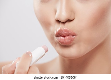 Girl with nude make up and naked shoulders posing at grey background, skin care concept, beauty photo, close up portrait, using lipstick and showing lips.