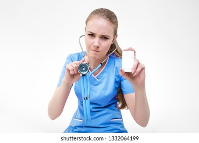 Girl nurse doctor blonde on a gray background one beautiful woman looks pill bank hand. Angry forcibly negative will feed. Violence coercion  client patient.