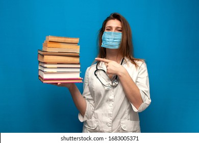girl nurse in a medical mask holds a stack of books, news and information about coronavirus, concept, copy space