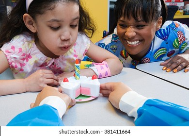 Girl and nurses with toy birthday cake