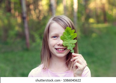 Girl with oak leaf in hand, covering her one eye