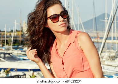 Girl observes boats in port. Woman watching the sunset by sunglasses