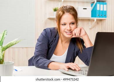 girl in the office in a good mood works on a computer