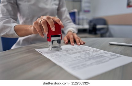 girl in the office puts a stamp on the documents