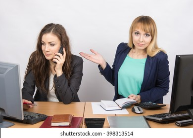 The girl in the office puzzled indicates colleague talking on the phone