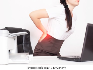 girl office worker holding her aching back from a chair, the concept of back pain in office workers, lactic acid in muscles and spinal problems, lumbago
