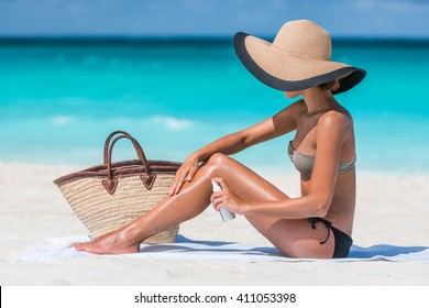 Girl oil spray tanning her legs protection from the sun's uv rays putting sunscreen lotion sunblock Unrecognizable girl with her beach essentials for a summer holiday - straw sun hat and tote bag.