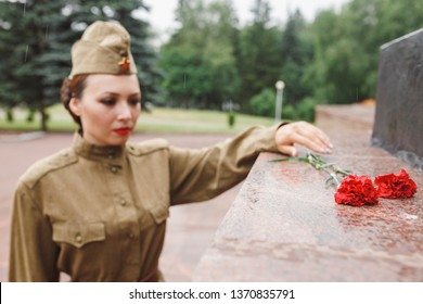 A girl in an old Soviet military uniform laying flowers at the monument to fallen soldiers in world War II
