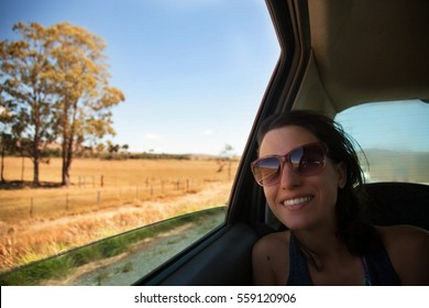 A girl on a back sit of the car, happy to travel on a country road