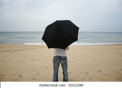 girl on back with an umbrella on the beach in a rainy day