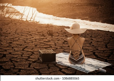 Girl on a background of dried up soil. Global warming.