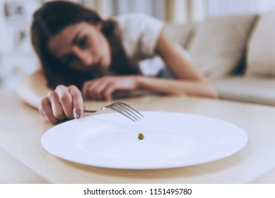 Girl on Background Try to Eat. Pea from Empty Plate. Closeup Plate. Woman Exhausted from Malnutrition. Laying on the Sofa. Anorexia Concept. Unhealthy Nutrition. Trying Reach. Loss Weight.