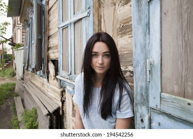 Girl on a background of a wooden house built in the early twentieth century