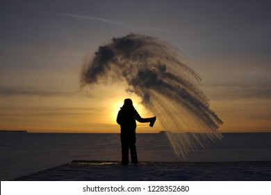 Girl on the bank of the winter sea at sunset. Woman splashes boiling water on cold air.