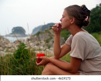 girl on the beach with coffee and cigarette