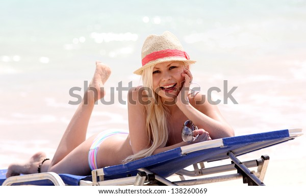 girl on the beach. glamorous sexy blonde on vacation. happy beautiful young woman with summer hat