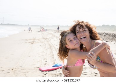 girl on the beach jumps into her mother's arms