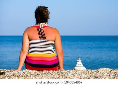 Girl on the beach meditating, holding stones