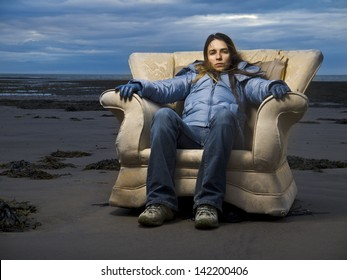 Girl on the beach sitting in an old armchair like a throne.