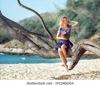 girl on the beach sitting on a palm tree with pineapple