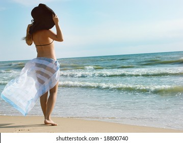 The girl on a beach stands by a back