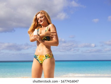 Girl on the beach with sunscreen. Beautiful blonde on the beach. Sun protection