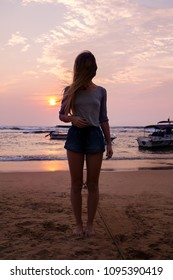 Girl on the beach on a sunset background