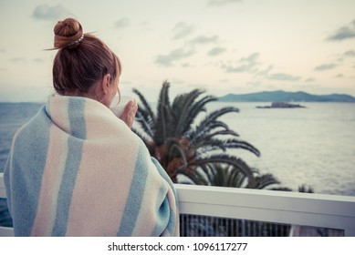 girl on the beach, woman on the sea. girl wrapped in warm blanket woke up in the morning and drinks coffee. girl is standing on balcony with cup of tea and watching the sunset