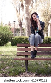 girl on a bench in a urban park talking at the phone and smiling