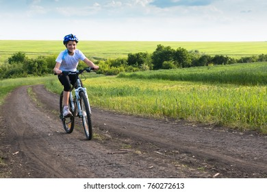 girl on a bicycle in summer rural landscape