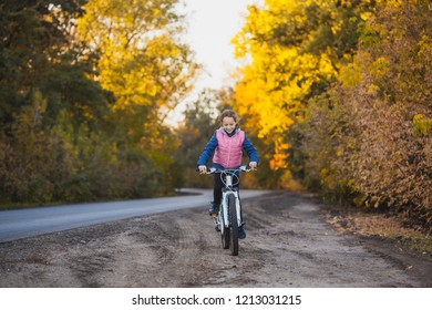 girl on a bicycle in the sunny autumn forest. happy girl cycling outdoors