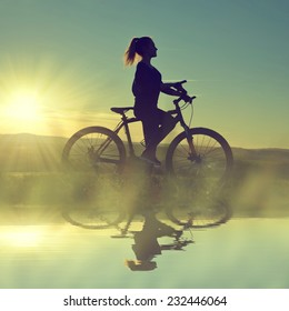 Girl on a bicycle in the sunset reflected on the water surface