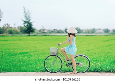 A girl on a bicycle in a traditional Vietnamese hat stands on the road and admires the rice fields.The girl rides a bicycle in a traditional Vietnamese hat in the midst of rice fields, Hoi An, Vietnam