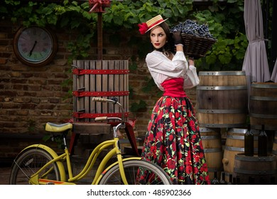 Girl on bike brought a basket full of grapes at the distillery in order to squeeze the juice and make wine.