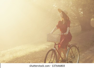 Girl on a bike in the countryside in sunrise time.