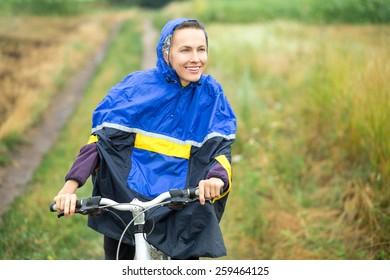Girl on bike enjoy her riding in rainy day